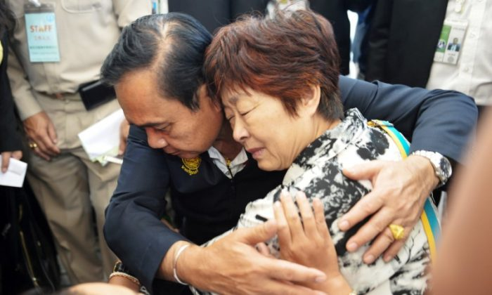 Thailand's Prime Minister Prayuth Chan-ocha comforts a relative of Chinese tourists involved in a sunken tourist boat accident at a hospital in Phuket, Thailand, July 9, 2018. (Reuters/Sooppharoek Teepapan)