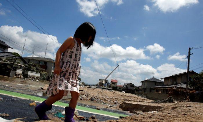 A local resident walks in a flood affected area in Mabi town in Kurashiki, Okayama Prefecture, Japan, July 10, 2018. (Reuters/Issei Kato)