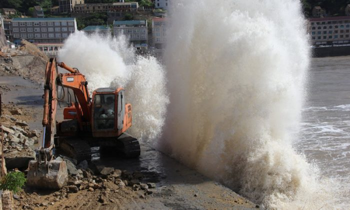 A wave breaks on the waterfront next to an excavator, as super typhoon Maria approaches, in Taizhou, Zhejiang province, China, July 10, 2018.  (REUTERS/Stringer)