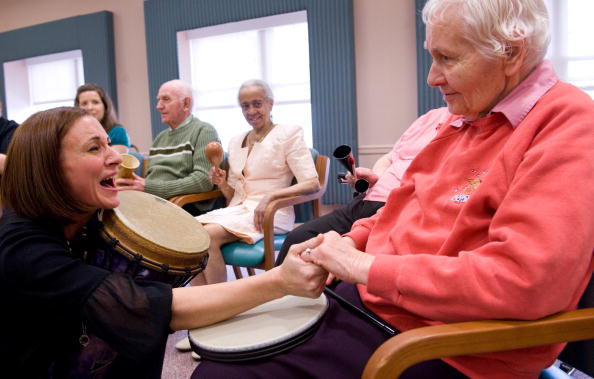 Music therapist Heather Davidson (L) greets Kathy McCullough (R) as she leads a drum circle with patients with Alzheimer's disease at the Copper Ridge Care Center in Sykesville, Maryland, on Oct. 23, 2009. (Photo credit should read SAUL LOEB/AFP/Getty Images)