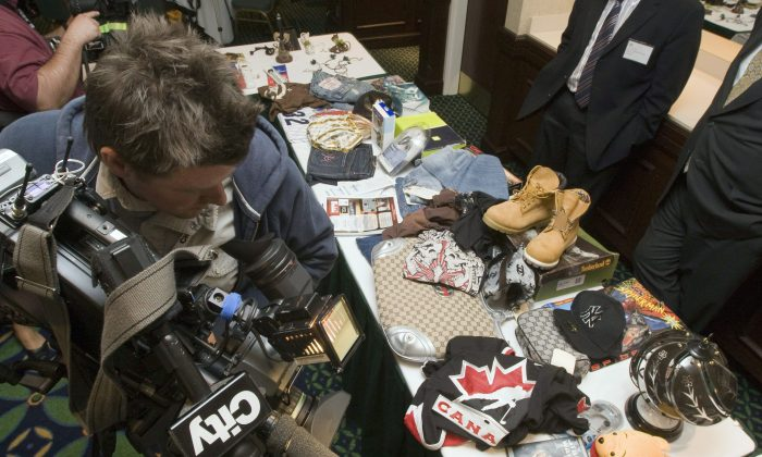 Television cameraman Jeff Ducharme shoots a display of counterfeit goods at a Canadian Anti-Counterfeiting Network conference in Toronto in this file photo. Anything can be counterfeit, from children's stuffed animals to electronics. (THE CANADIAN PRESS/Frank Gunn)