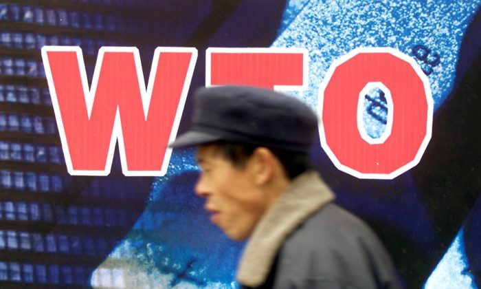 A Chinese man walks past a billboard promoting the country's membership to the World Trade Organization (WTO), in Beijing, on December 10, 2001. (Goh Chai Hin/AFP/Getty Images)