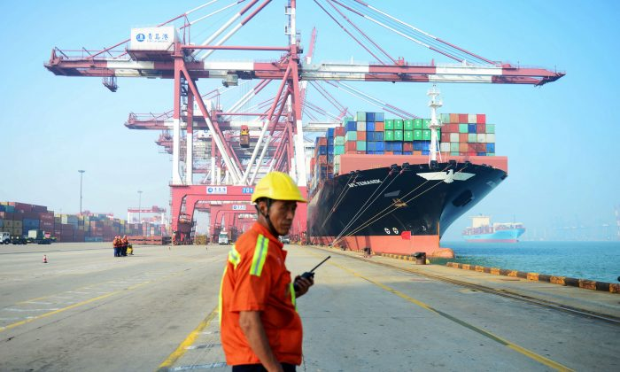 A Chinese worker looks on as a cargo ship is loaded at a port in Qingdao, Shandong Province, China on July 13, 2017.(STR/AFP/Getty Images)
