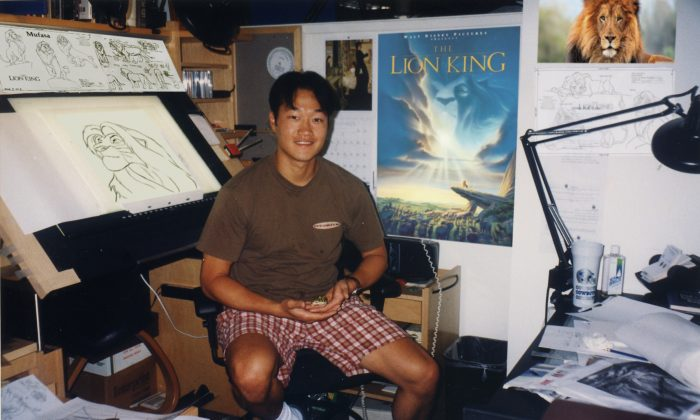 "An old photo of Davy Liu in his office at Disney, with a poster of ""The Lion King"" behind him. ""The Lion King"" was one of Liu's favorite projects. (Courtesy of Davy Liu)"