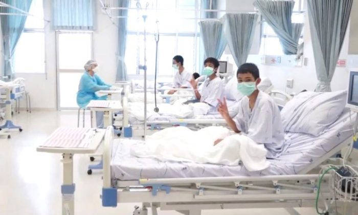 FILE PHOTO: A screen grab shows boys rescued from the Thai cave wearing mask and resting in a hospital in Chiang Rai, Thailand from a July 11, 2018 handout video.    (Government Public Relations Department (PRD) and Government Spokesman Bureau/Handout via Reuters TV)