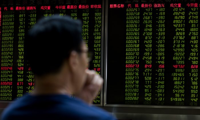 A man sits in front of a screen showing stock prices at a securities brokerage in Beijing on July 11. (Nicolas Asfouri/ AFP/Getty Images)