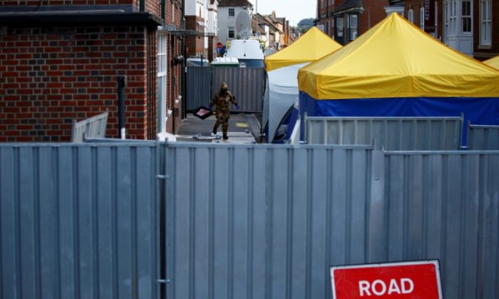 A forensic investigator, wearing a protective suit, emerges from the rear of John Baker House, after it was confirmed that two people had been poisoned with the nerve-agent Novichok, in Amesbury, Britain, July 6, 2018. (Reuters/Henry Nicholls/File Photo)