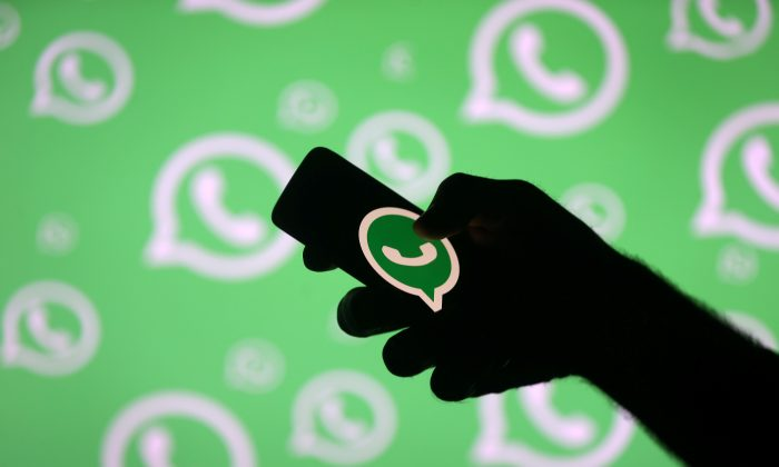 A man poses with a smartphone in front of displayed Whatsapp logo in this illustration September 14, 2017. (Reuters/Dado Ruvic/File photo)