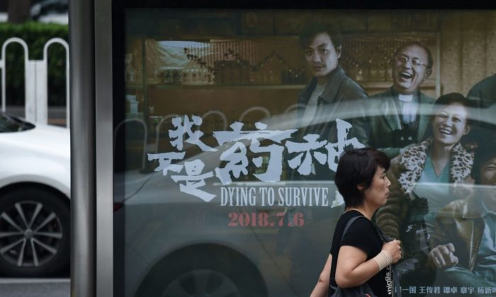 "A woman walks past a poster of the film ""Dying to Survive"" at a bus stop in Beijing on July 12, 2018. (Wang Zhao/AFP/Getty Images)"