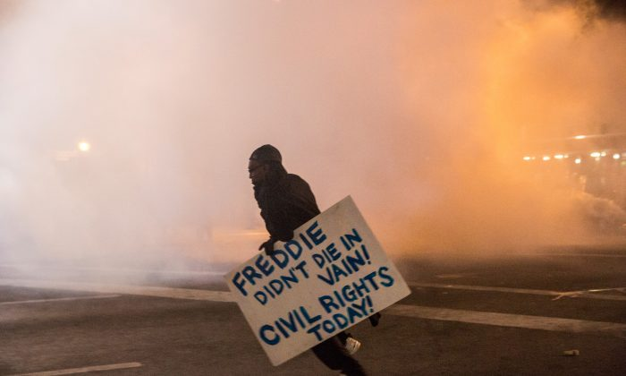 A protester walks through tear gas as police enforce a mandatory, city-wide curfew on April 28, 2015 in Baltimore, Maryland. (Andrew Burton/Getty Images)