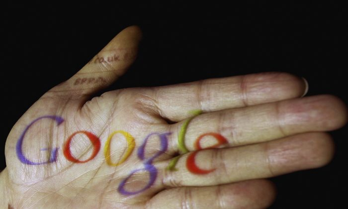 In this photo illustration, the logo of the multi-faceted internet giant Google is seen projected onto the palm of a hand in Glasgow, Scotland.  (Jeff J. Mitchell/Getty Images)