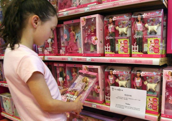 """A young girl holds a Barbie doll next to a notice saying that the toy """"Barbie and Tanner"""" made by US toy giant Mattel, which has just been recalled in the US, is out of stock at a Toys """"R"""" Us store in Shanghai, Aug.15 2007.  (Photo credit should read MARK RALSTON/AFP/Getty Images)"""