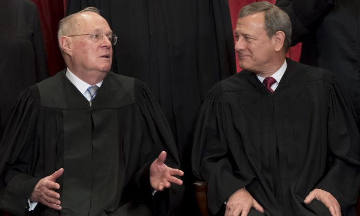 Chief Justice of the United States John G. Roberts (R) and U.S. Supreme Court Associate Justice Anthony M. Kennedy (L) sit for an official photo with other members of the U.S. Supreme Court in Washington, June 1, 2017. (Saul Loeb/AFP/Getty Images)
