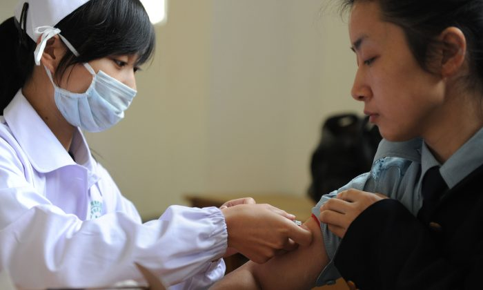 A Chinese nurse inoculates a woman with the swine flu vaccine at a hospital in Hefei City, in eastern China's Anhui Province on November 10, 2009. (STR/AFP/Getty Images)