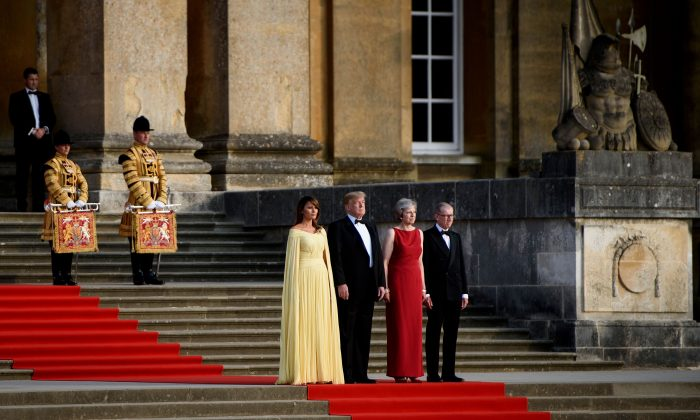 First Lady Melania Trump, President Donald Trump, UK Prime Minister Theresa May, and her husband Philip May stand on the steps in the Great Court to watch the bands of the Scots, Irish, and Welsh Guards perform a ceremonial welcome at Blenheim Palace, west of London, on July 12, 2018. (BRENDAN SMIALOWSKI/AFP/Getty Images)