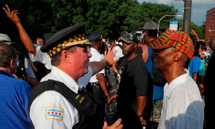 Chicago police officers try to direct protestors during a march through the streets to protest the fatal shooting of Harith Augustus by a Chicago police officer in Chicago on July 15, 2018. (Jim Young/AFP/Getty Images)