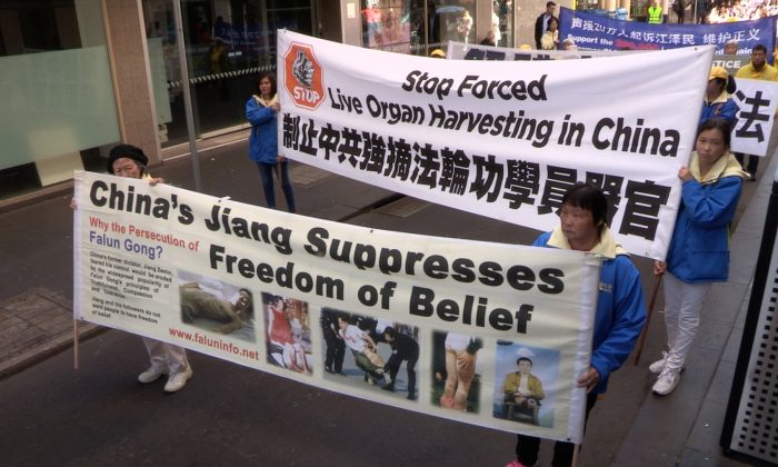 Falun Dafa practitioners holding banners raising awareness about forced organ harvesting and bringing Jiang Zemin to justice, in Melbourne, Australia on 14 July 2018. (Daniel Cameron/NTD)