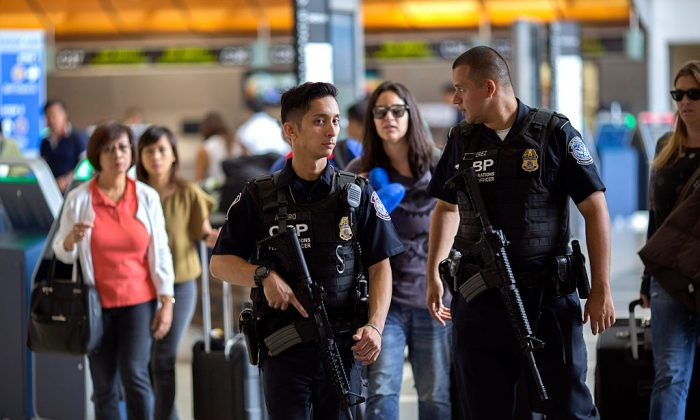 U.S. Customs and Border Protection officials watch over travelers at Los Angeles International Airport on July 2, 2016. (David McNew/Getty Images)