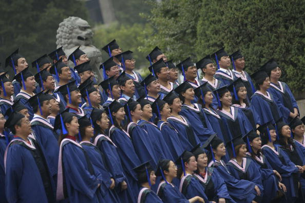 Master's degree graduates pose for pictures during a graduation ceremony at Peking University in Beijing on June 24, 2006. (China Photos/Getty Images)