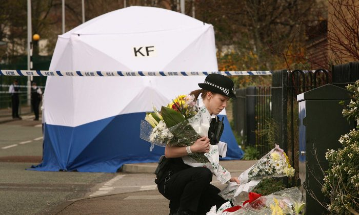 A police woman places floral tributes near a tent covering the murder scene in Leytonstone in north-east London on April 7, 2007. (Peter Macdiarmid/Getty Images)