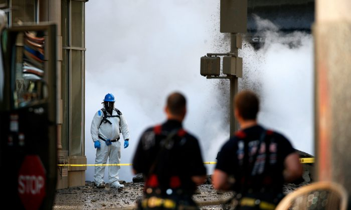 New York Fire Department watch as an emergency responder examines the scene near a steam pipe explosion in Midtown Manhattan, New York City, U.S., July 19, 2018.  (Reuters/Brendan McDermid)