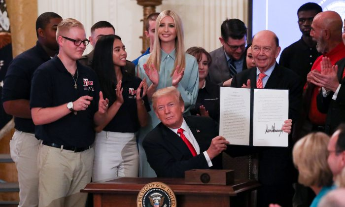 """President Donald Trump signs an executive order during the """"Pledge to America's Workers"""" event in the East Room of the White House on July 19, 2018. (Samira Bouaou/The Epoch Times)"""