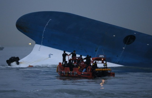 """FILE PHOTO: Maritime police search for missing passengers in front of the South Korean ferry """"Sewol"""" which sank at the sea off Jindo April 16, 2014. (Reuters/Kim Hong-Ji/File Photo)"""