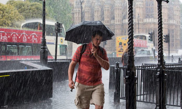 A man wearing shorts and holding an umbrella walks through heavy rain in Westminster in this file photo. (Jack Taylor/Getty Images)