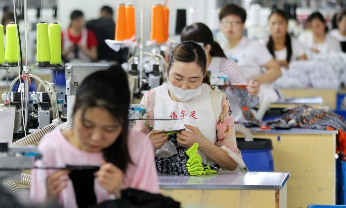 Employees work on socks that will be exported at a factory in Huaibei, Anhui province on June 22 (-/AFP/Getty Images)