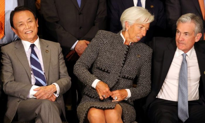 International Monetary Fund (IMF) Managing Director Christine Lagarde sits alongside Jerome Powell, Chairman of the U.S. Federal Reserve, and Japan's Minister of Finance Taro Aso as they pose for the official photo at the G20 Meeting of Finance Ministers in Buenos Aires, Argentina on July 21, 2018. (REUTERS/Marcos Brindicci)
