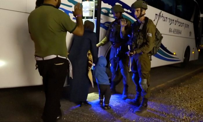 People walk past Israeli soldiers as they board a bus during the Syria Civil Defence, also known as the White Helmets, extraction from the Golan Heights, Israel in this still image taken from video, provided by the Israeli Army on July 22, 2018. (Israeli Army Handout via REUTERS)