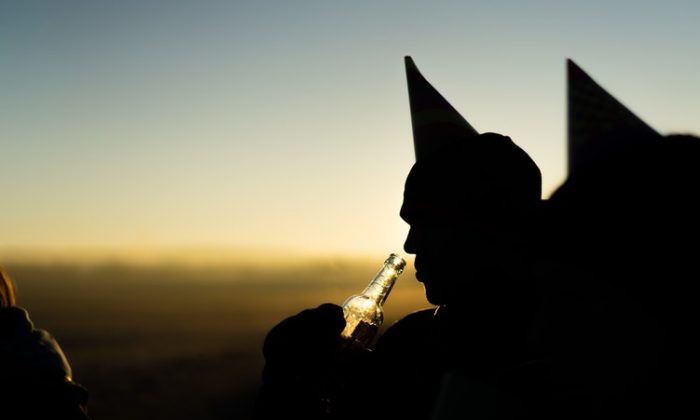 A silhouette of a man drinking from a beer bottle wearing a party hat (Unsplash).