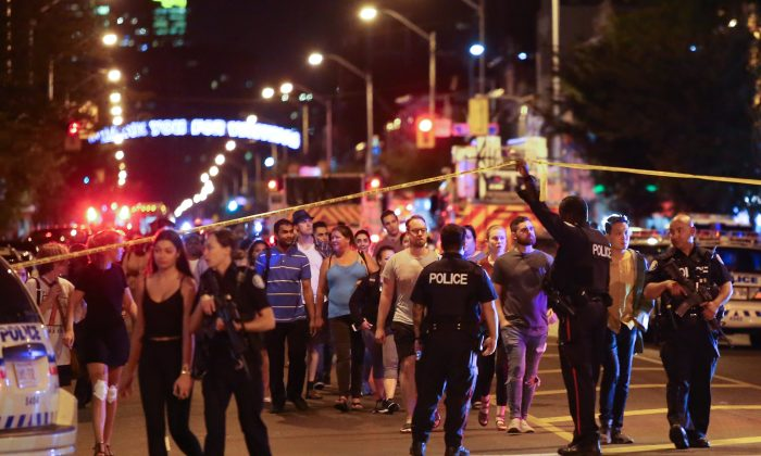 People leave an area taped off by the police near the scene of a mass shooting in Toronto, Canada, July 22, 2018. (Reuters/Chris Helgren)