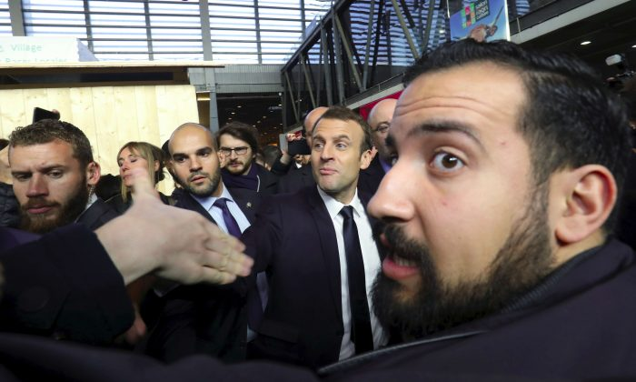 French President Emmanuel Macron shakes hands while visiting the 55th International Agriculture Fair, as Elysee senior security officer Alexandre Benalla (R) looks on at the Porte de Versailles exhibition center in Paris, France, Feb. 24, 2018. (LudovicMarin/Pool via Reuters)