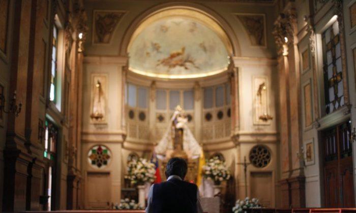 A Roman Catholic faithful prays during Mass at Santiago Cathedral in Santiago, February 16, 2013. (Reuters/Ivan Alvarado)