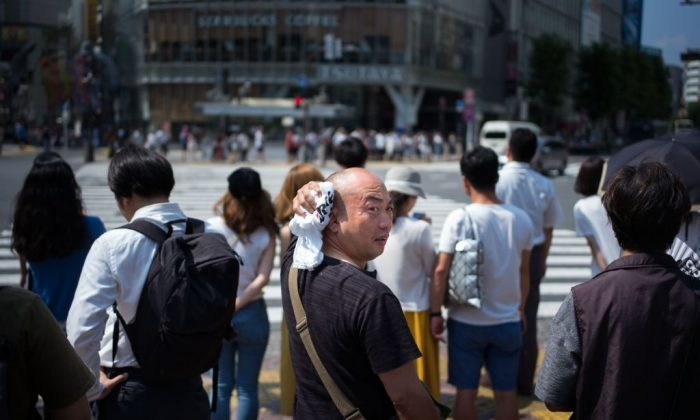 A man wipes perspiration from his head in Tokyo on July 24, 2018, as Japan suffers from a heatwave. (MARTIN BUREAU/AFP/Getty Images))