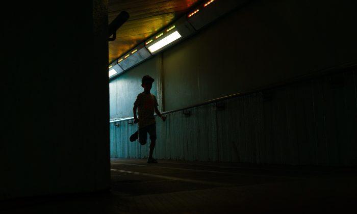 A boy runs down a dark hall. (Unsplash)