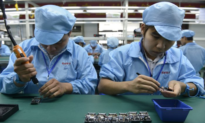Chinese workers assemble electronic parts a factory in Shenzhen, in southern China's Guangdong province in this file photo.  (STR/AFP/Getty Images)