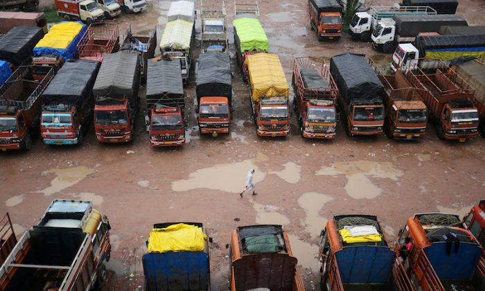 A driver walks past parked trucks inside a depot during a nationwide strike in Ahmedabad, India, July 20, 2018. (REUTERS/Amit Dave/File photo)