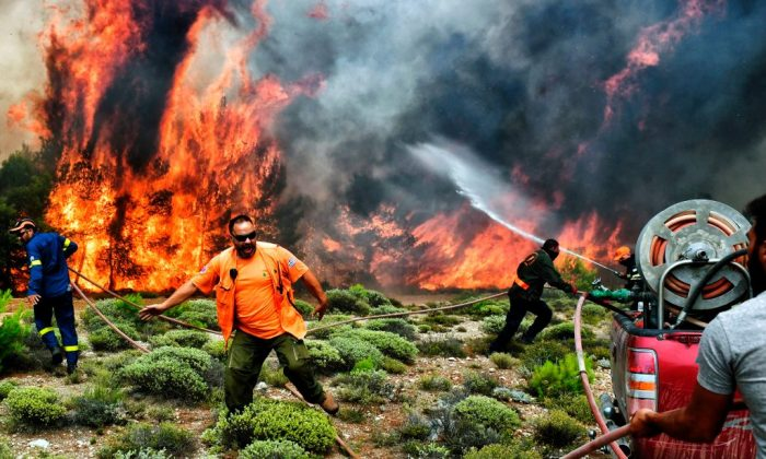 Firefighters and volunteers try to extinguish flames during a wildfire at the village of Kineta, near Athens, on July 24, 2018. (Valerie Gache/AFP/Getty Images)