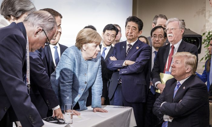 German Chancellor Angela Merkel speaks to President Donald Trump in front of other world leaders in Charlevoix, Canada, at the G-7 summit on June 9, 2018. The mainstream media and world leaders are blaming Trump for starting a trade war, where in reality all politicians are fighting to protect their special interest groups.    (Jesco Denzel /Bundesregierung via Getty Images)