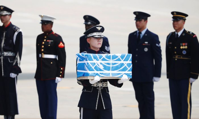 A soldier carries a casket containing the remains of a U.S. soldier who was killed in the Korean War during a ceremony at Osan Air Base in Pyeongtaek, South Korea, July 27, 2018.    (Reuters/Kim Hong-Ji/Pool)