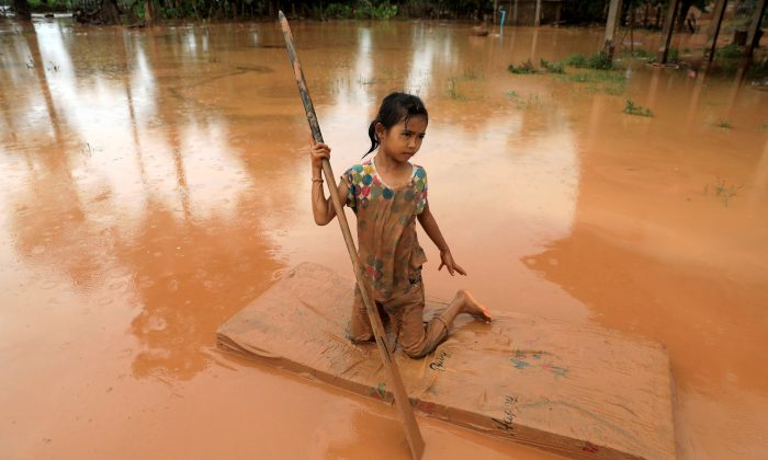 A girl uses a mattress as a raft during the flood after the Xepian-Xe Nam Noy hydropower dam collapsed in Attapeu province, Laos July 26, 2018. (Reuters/Soe Zeya Tun)