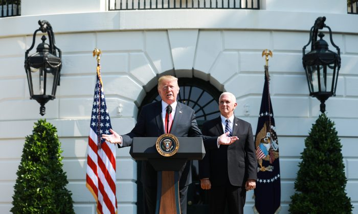 President Donald Trump delivers remarks, as Vice President Mike Pence looks on, about the economy and second quarter GDP growth of 4.1% on the South Lawn of the White House in Washington on July 27, 2018. (Samira Bouaou/The Epoch Times)