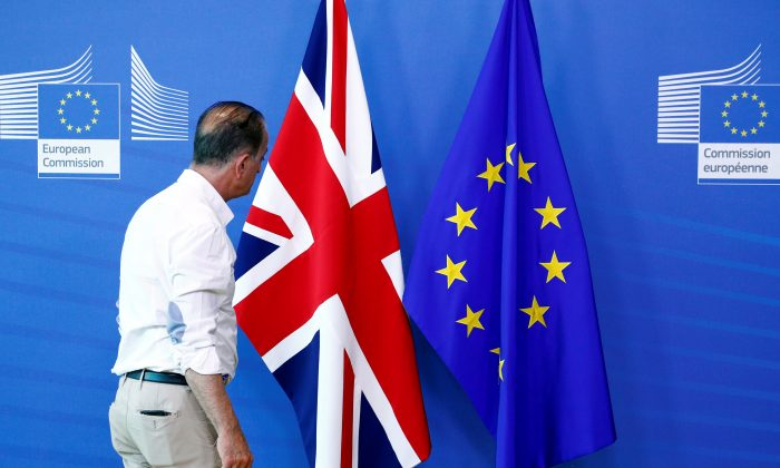 An official inspects a Union Jack flag next to the European Union flag, ahead of a meeting between Britain's Secretary of State for Exiting the European Union, Dominic Raab, and European Union's chief Brexit negotiator, Michel Barnier, at the EU Commission headquarters in Brussels, Belgium July 19, 2018. (REUTERS/Francois Lenoir)