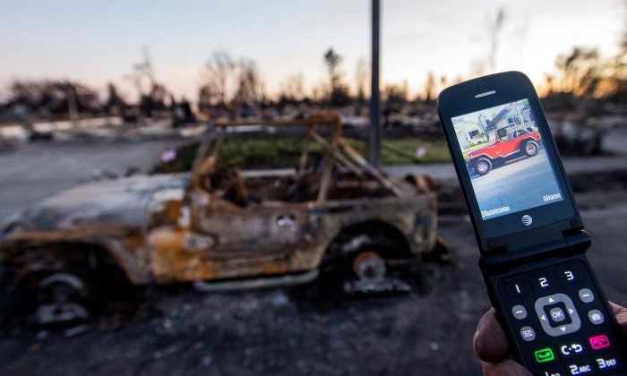 A man shows a photo of his burned Jeep on his cell phone in Santa Rosa, California on October 20, 2017. (JOSH EDELSON/AFP/Getty Images)