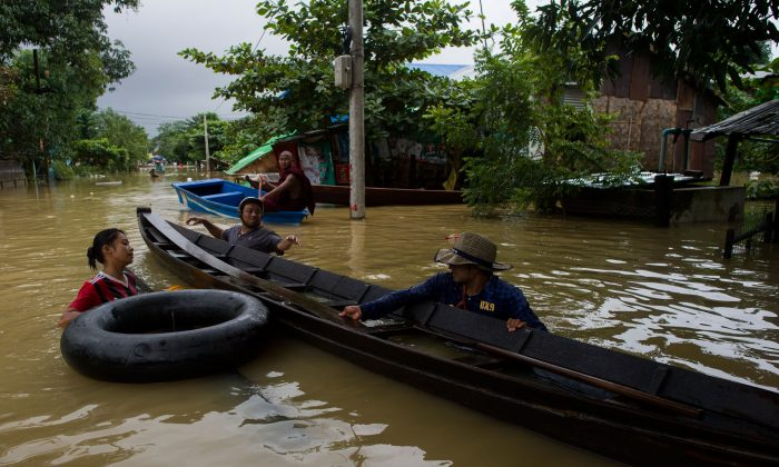 People travel through floodwaters in the Bago region in Burma (also known as Myanmar), some 68 kilometers away from Yangon, on July 29, 2018. Heavy monsoon rains have pounded Karen state, Mon state and Bago region in recent days and show no sign of abating, raising fears that the worst might be yet to come. (Ye Aung Thu/AFP/Getty Images)