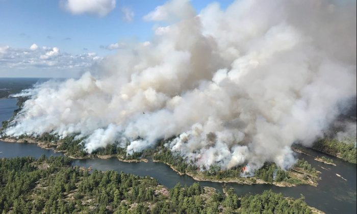 An aerial view taken over the Parry Sound 33 fire is shown in this handout image. The blaze, known as Parry Sound 33, sprung up on July 18. Ontario firefighters have been fighting it with the help of their counterparts from other provinces, as well as the United States and Mexico. (The Canadian Press/HO-AFFES Ignition/Response Specialist-Dan Leonard)
