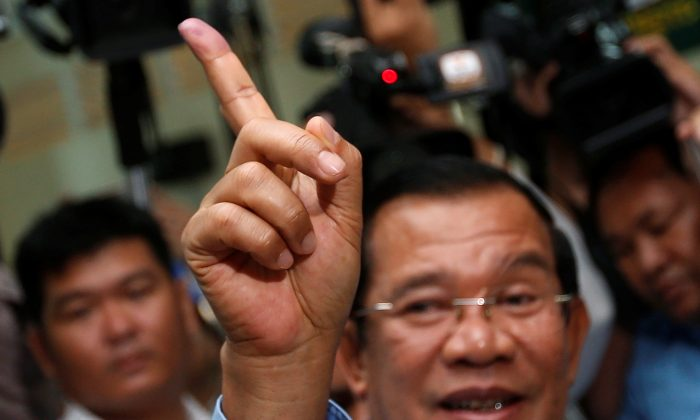 Cambodia's Prime Minister and President of the Cambodian People's Party (CPP) Hun Sen shows his stained finger at a polling station during a general election in Takhmao, Kandal province, Cambodia July 29, 2018. (Reuters/Samrang Pring)