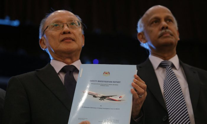 MH370 safety investigator-in-charge Kok Soo Chon shows the MH370 safety investigation report booklet to the media after a news conference in Putrajaya, Malaysia July 30, 2018. (REUTERS/Sadiq Asyraf)
